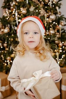 Cute dziewczynka w kapeluszu świętego mikołaja pod choinką z obecnym pudełkiem. wesołych świąt, nowego roku. przytulny ciepły zimowy wieczór w domu. boże narodzenie