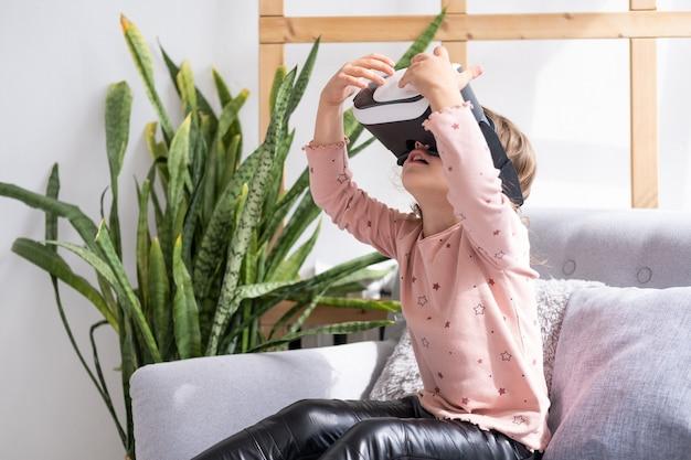 Cute dziewczynka w okularach wirtualnej rzeczywistości w domu. szczęśliwe dziecko za pomocą zestawu słuchawkowego vr.