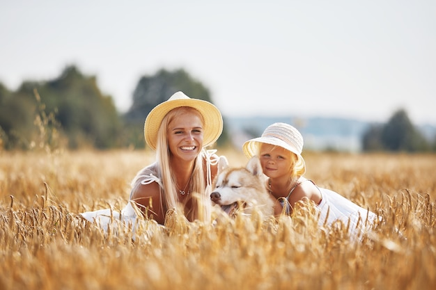 Cute dziewczynka z mamą i psem na polu pszenicy. szczęśliwa młoda rodzina spędza czas razem na łonie natury. mama, mała dziewczynka i pies husky odpoczywa na świeżym powietrzu. pojęcie wspólnoty, miłości, szczęścia.