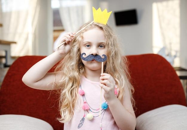 Cute dziewczynka z papieru korony i wąsy siedząc na czerwonym krześle w domu.