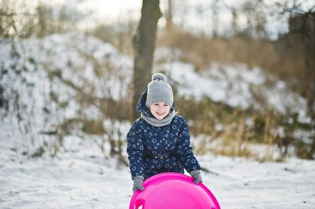 Cute dziewczynka z spodkiem sanki na zewnątrz w zimowy dzień.
