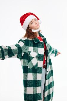Cute girl maska medyczna ubrania świąteczne ręce po bokach jasnym tle