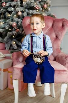 Cute kid play. dziecko z prezentem. chłopiec z prezentem na boże narodzenie. mały chłopiec bawi się pod choinką. dziecko z prezentem świątecznym w domu. urządzony dom na ferie zimowe. uroczystość z dziećmi
