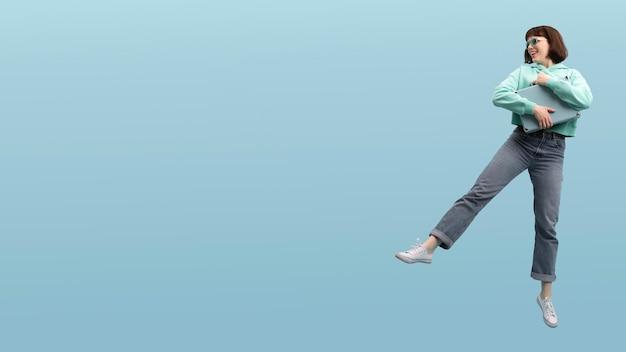 Cute kobieta skoki na białym tle na niebiesko z miejsca na kopię