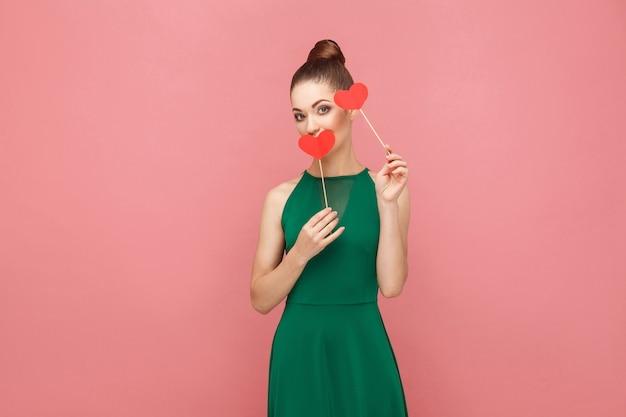 Cute kobieta trzyma dwa małe czerwone serce. koncepcja ekspresji emocji i uczuć. strzał studio, na białym tle na różowym tle