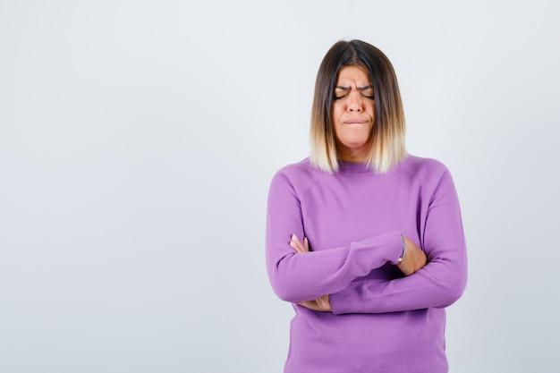 Cute kobieta trzymając ręce złożone w fioletowy sweter i ponury. przedni widok.