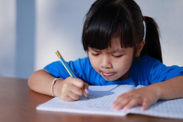 Cute little asian girl pisze książkę ołówkiem na stole