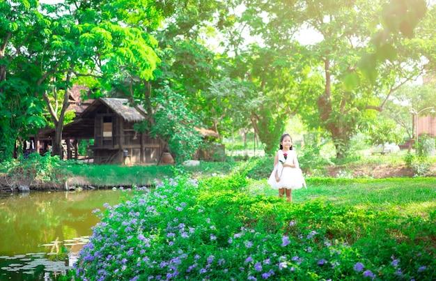 Cute little asian girl w białej sukni stojącej i trzymając czerwoną różę w parku