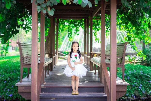 Cute little asian girl w białej sukni trzymając czerwoną różę stojącą w pawilonie