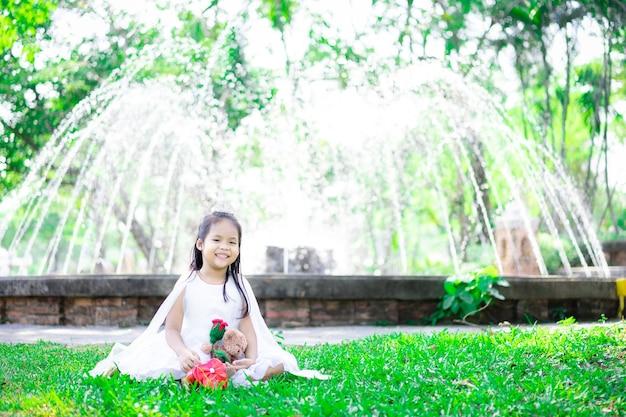 Cute little asian girl w białej sukni z czerwoną różą i prezentem w parku