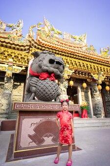Cute little asian girl w chińskiej tradycyjnej sukni, uśmiechając się i stojąc w pobliżu posągu. koncepcja szczęśliwego chińskiego nowego roku.