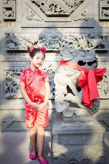 Cute little asian girl w chińskiej tradycyjnej sukni, uśmiechając się i stojąc w pobliżu posągu.