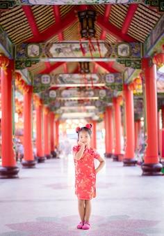 Cute little asian girl w chińskim tradycyjnym stroju, uśmiechając się i stojąc w świątyni. koncepcja szczęśliwego chińskiego nowego roku.