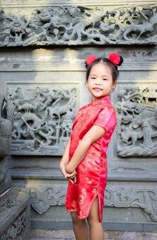 Cute little asian girl w chińskim tradycyjnym stroju, uśmiechając się i stojąc w świątyni.