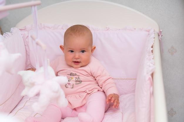Cute little baby girl siedzi w różowym łóżeczku patrząc z ciekawością na aparat w widoku z bliska
