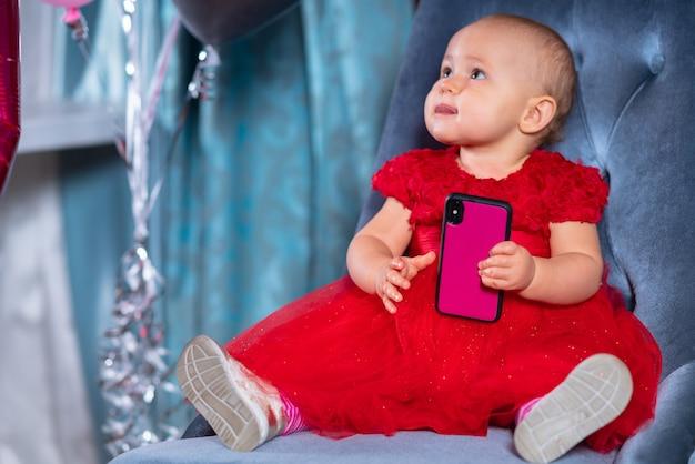 Cute little baby girl w świątecznej czerwonej sukience wakacje, siedząc na niebieskim aksamitnym krześle