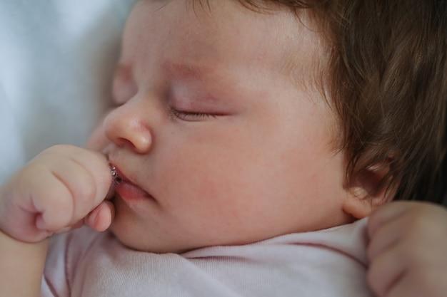 Cute little baby girl z ciemnymi włosami leżącego snu na białą kratę. koncepcja opieki nad dzieckiem i macierzyństwa. ręka w usta. nowe życie. szczęśliwa rodzina. w domu. miłość. słodki. czułość.