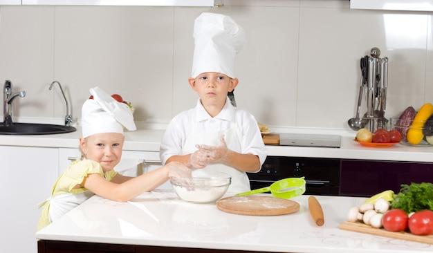 Cute little chefs pieczenia pizzy w kuchni