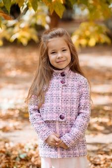 Cute little girl 5 lat z jesiennych liści pomarańczy jesienią w parku