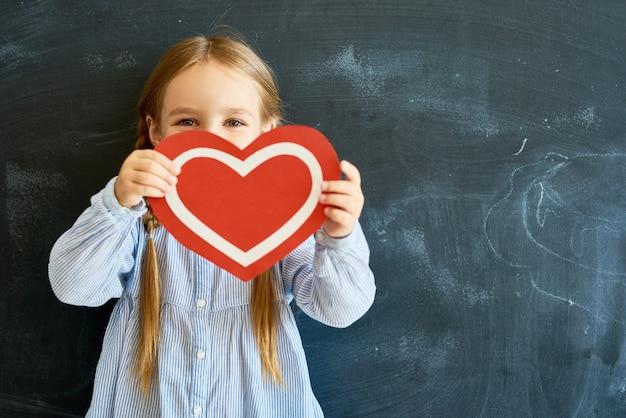 Cute little girl gospodarstwa papierowe serce