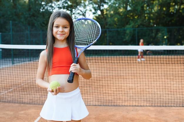 Cute little girl gry w badmintona na zewnątrz w ciepły i słoneczny letni dzień