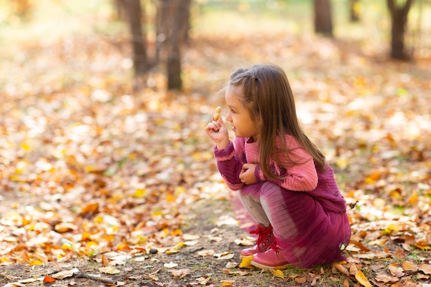 Cute little girl hld peanut w jesienny park z pomarańczowymi liśćmi