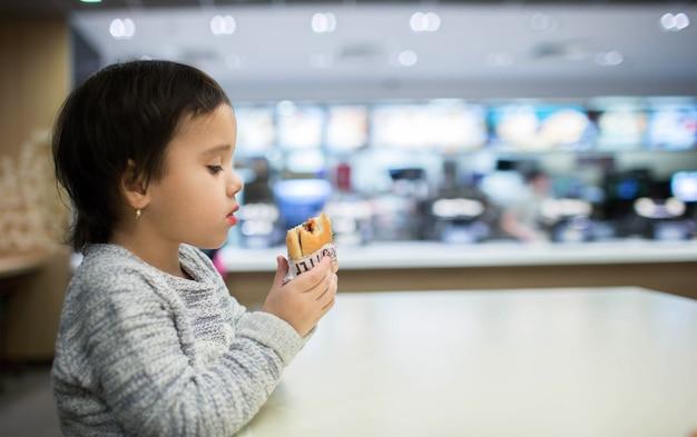 Cute little girl jedzenie hamburgera w fast food
