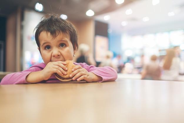 Cute little girl latin jedzenie hamburgera i patrząc w kierunku miejsca na kopię