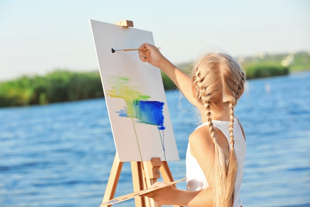 Cute little girl malowanie obrazu, na zewnątrz