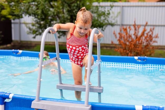 Cute little girl przygotowuje się do skoku do błękitnej wody, zabawy w basenie
