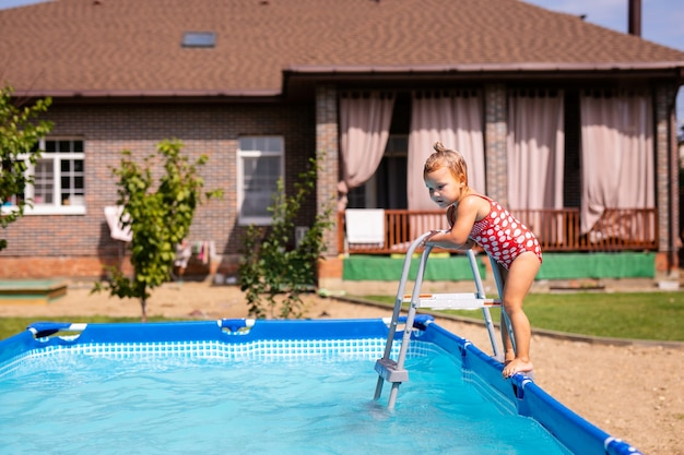 Cute little girl przygotowuje się do skoku do niebieskiej wody