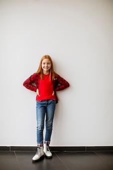Cute little girl rude włosy stojąc przy białej ścianie