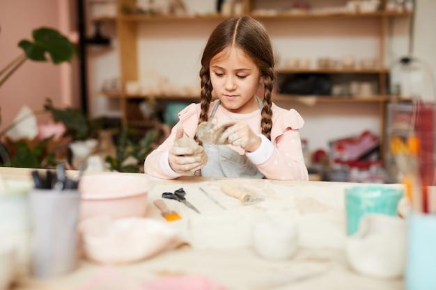 Cute little girl shaping clay