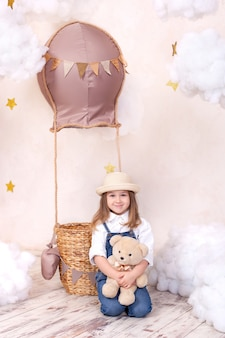 Cute little girl siedzi na podłodze i przytrzymaj misia. dziewczynka bawi się w pokoju dziecięcym zabawką.