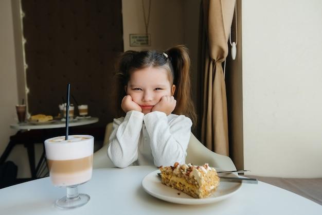 Cute little girl siedzi w kawiarni i patrząc na zbliżenie ciasta i kakao. dieta i prawidłowe odżywianie.