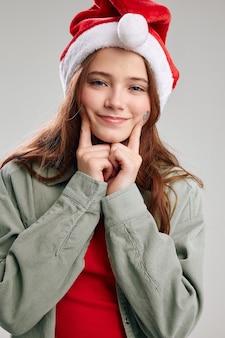 Cute little girl w czerwoną czapkę szczegół portret szarym tle. wysokiej jakości zdjęcie