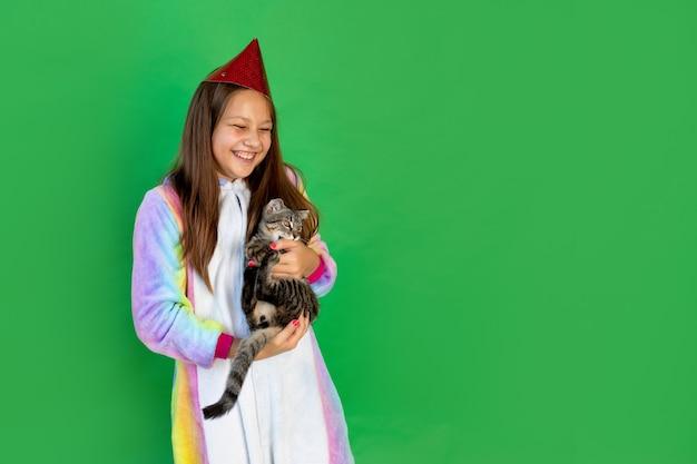 Cute little girl w czerwonym mickey mouse bawi się z kotem