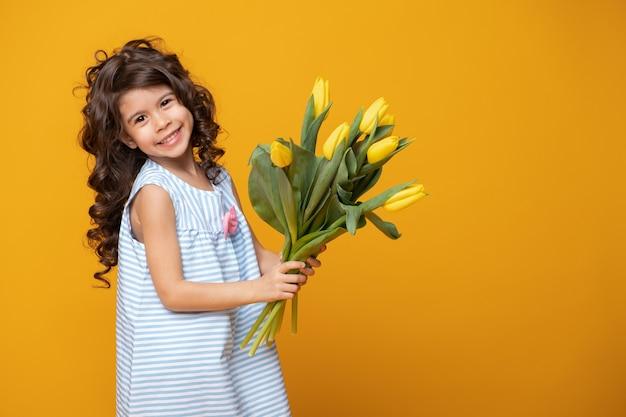 Cute little girl w paski sukienka trzyma bukiet tulipanów na żółtym tle studio. wiosenny dzień kobiety.