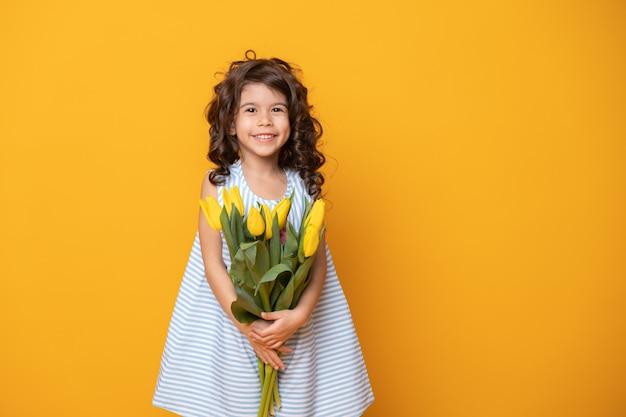 Cute little girl w paski sukienka trzyma bukiet tulipanów na żółtym tle studio
