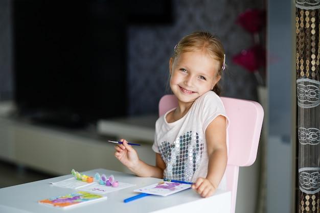 Cute little girl z blond włosami malowanie obrazu w domu.