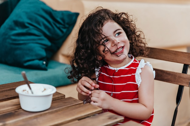 Cute little girl z kręconymi włosami siedzi w restauracji na świeżym powietrzu. portret całkiem dziecko jedzenie lodów w kawiarni.