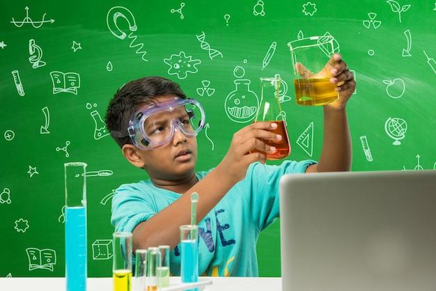 Cute little indian asian school boy uczeń eksperymentujący lub studiujący naukę w laboratorium, na tle zielonej tablicy z edukacyjnymi doodles