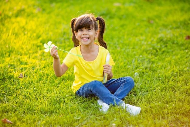 Cute little indian girl lato na trawniku dmuchanie baniek mydlanych