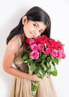 Cute little indian girl trzyma kilka lub bukiet świeżych czerwonych róż lub kwiatów gulab. pojedynczo na białym tle