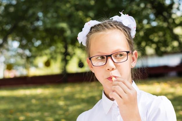 Cute little school girl w okularach zjada frytki na pikniku w parku. szkolne posiłki