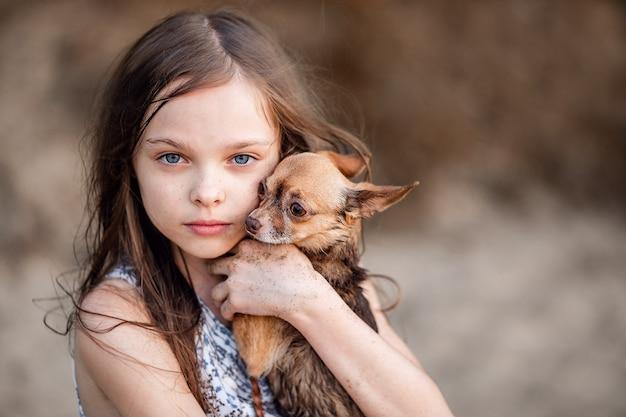 Cute little teen girl przytula swojego psa. portret dziecka z chihuahua. dziewczyna z długimi włosami okazuje miłość i czułe uczucia do zwierzaka. pełnokrwisty pies w rękach właściciela.
