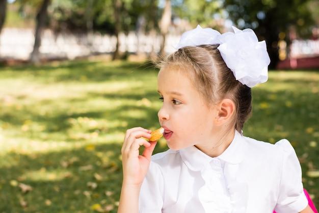 Cute little uczennica jedzenie bryłek apetyczny na pikniku w parku. szkolne posiłki. skopiuj miejsce