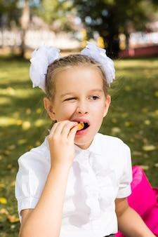 Cute little uczennica jedzenie bryłek apetyczny na pikniku w parku. szkolne posiłki. widok pionowy
