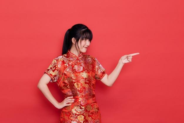 Cute młoda kobieta azji nosić cheongsam wskazując na puste dla koncepcji chińskiego nowego roku na czerwono