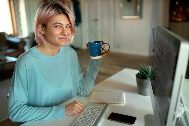 Cute młoda kobieta grafik pracuje nad zawartością wizualną strony internetowej, przy użyciu komputera stacjonarnego, pije herbatę, uśmiecha się do kamery